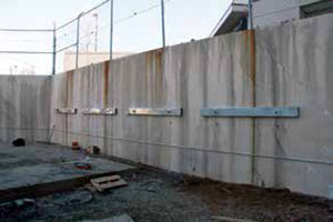 Helical tiebacks and tube steel walers stabilize concrete retaining wall